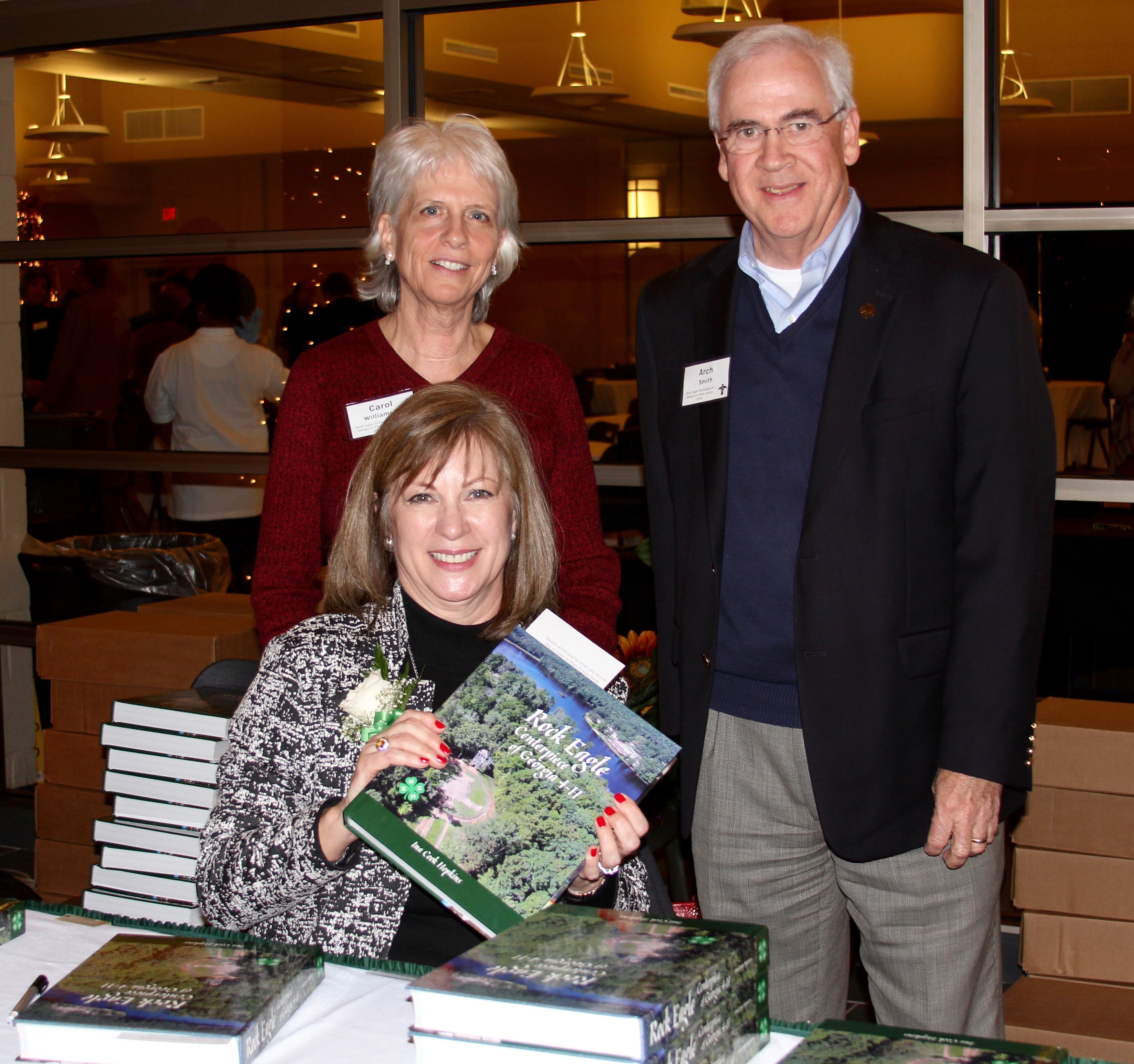 """It took author Ina Cook Hopkins more than nine years to compile data, interview key players, write the text and work with designer Carol Williamson to complete a history book about Rock Eagle 4-H Center. A former Walton County 4-H'er, Hopkins refers to the book as her last 4-H record book and a """"tangible way to give back to the organization that means so much"""" to her. She is pictured (seated) with the book's designer, Carol Williamson (standing left), and Georgia 4-H State Leader Arch Smith."""
