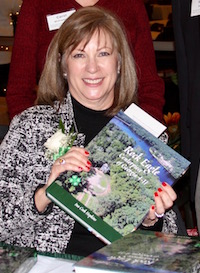 "It took author Ina Cook Hopkins more than nine years to compile data, interview key players, write the text and work with designer Carol Williamson to complete a history book about Rock Eagle 4-H Center. A former Walton County 4-H'er, Hopkins refers to the book as her last 4-H record book and a ""tangible way to give back to the organization that means so much"" to her. She is pictured (seated) with the book's designer, Carol Williamson (standing left), and Georgia 4-H State Leader Arch Smith."