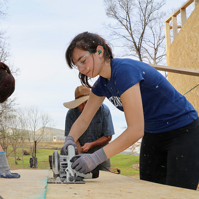 "Reilly Megee, a student in UGA's ""Green Building and the Tiny House Movement"" course, saws into a piece of plywood during a workday at UGArden."
