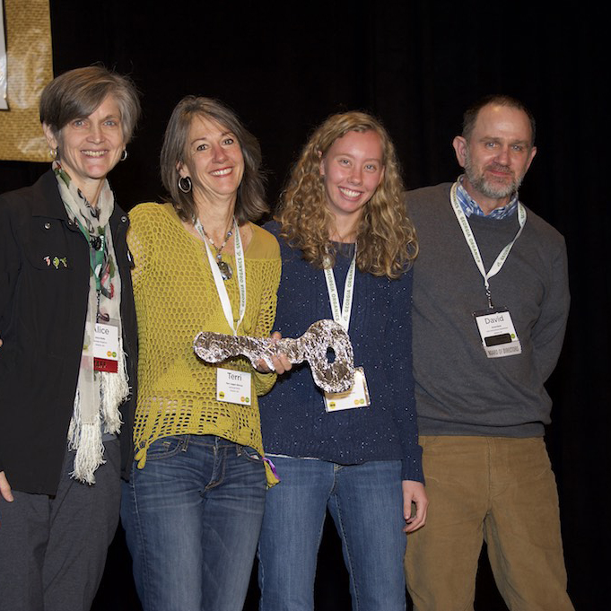 """Rabun County farmer Terri Jagger Blincoe receives the ceremonial """"key"""" to a tiny house funded by Georgia Organics and built by students in UGA's course on """"Green Building and the Tiny House Movement."""" Georgia Organics Executive Director Alice Rolls, far left, UGA student Emma Courson and UGA associate professor of horticulture David Berle congratulate her."""
