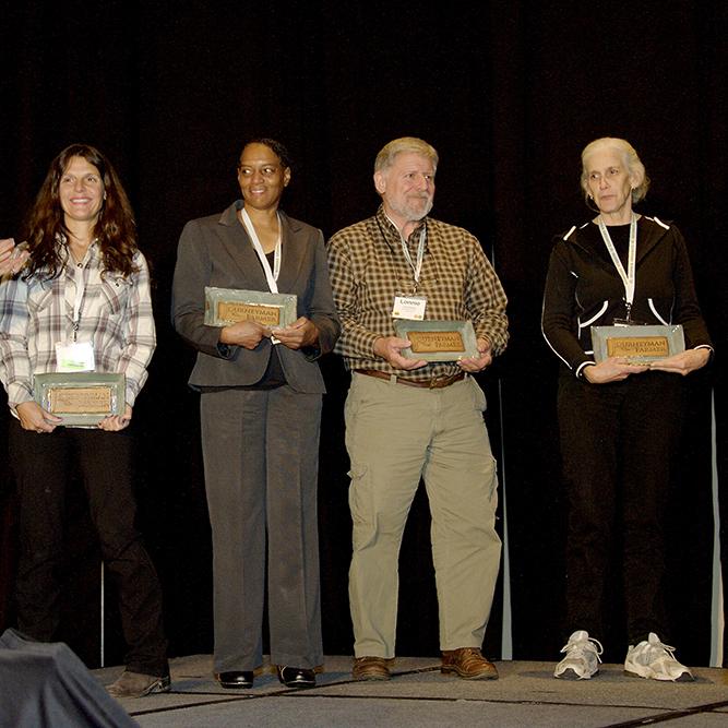 Georgia Organics Executive Director Alice Rolls applauds as Julie Best, Azalea Moss, Lonnie Edenfield and Martine Olsen receive their Journeyman Farmer Certificate Program plaques at the 20th Anniversary Georgia Organics Conference.