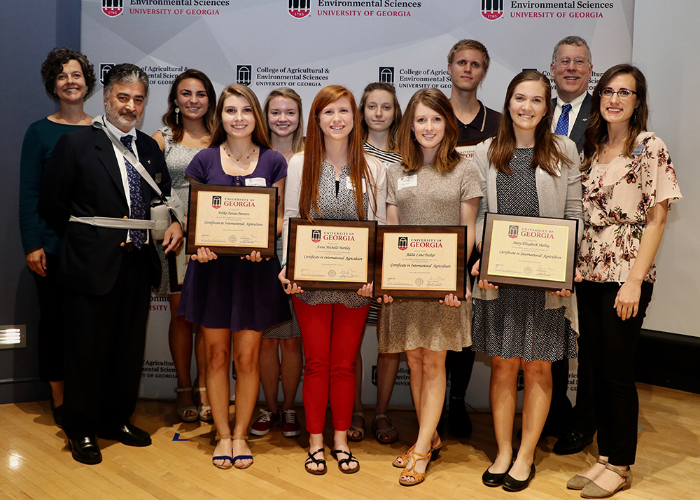 The UGA CAES Office of Global Programs recognized eight students for completing the college's Certificate in International Agriculture. From left, Assistant Director of the Office of Global Programs Vicki McMacken, and Director of the Office of Global Programs Amrit Bart, congratulate Carleen Porter, Tatum Monroe, Sarah Pate, Anna Hartley, Anna Trakhman, Addie Tucker, Aiden Holley and Mary Shelley with CAES Dean Sam Pardue and CAES Director of Experiential Learning Amanda Stephens.