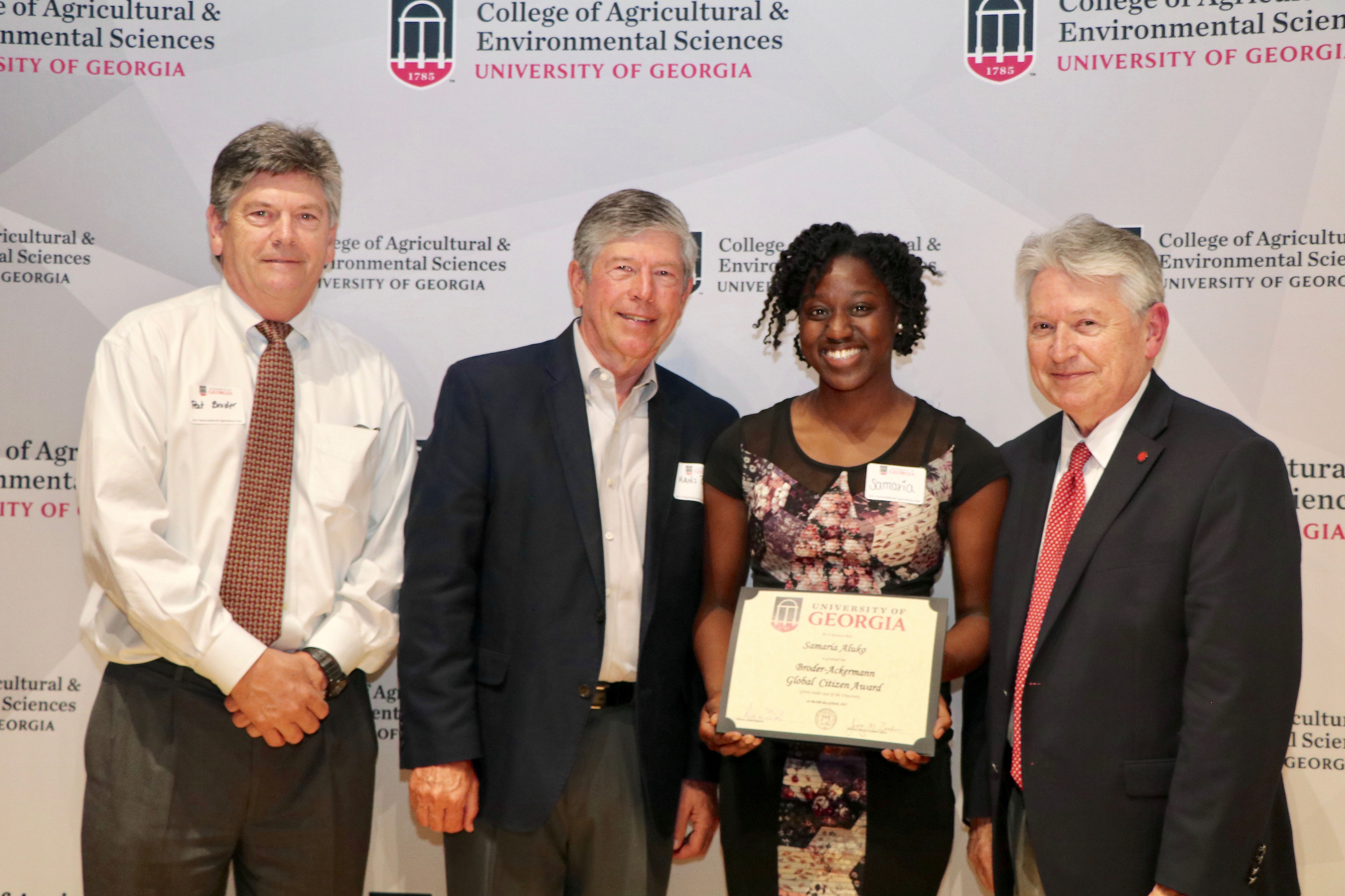 Patrick Broder and Hans Broder Jr., left, and Josef Broder, far right, congratulate Samaria Aluko, the inaugural winner of the Broder-Ackermann Global Citizen Award, on April 18 at CAES's seventh annual International Agriculture Day reception. Aluko will receive a $1,000 scholarship to support her work helping to provide health care to underserved communities.