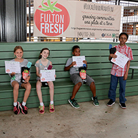 An exhausted but triumphant team of school-aged chefs — including Victoria Sweeney, 10, of Warren T. Jackson Elementary School; Parker Payne, 10, of Woodward Academy; Nile Smith, 10, of Roswell North Elementary School; and Isaiah Farrow, 10, of Georgia Connections Academy — celebrate after winning the inaugural Fulton Fresh Kids Cooking Competition on June 6 at the Ponce City Market Farmers Market.