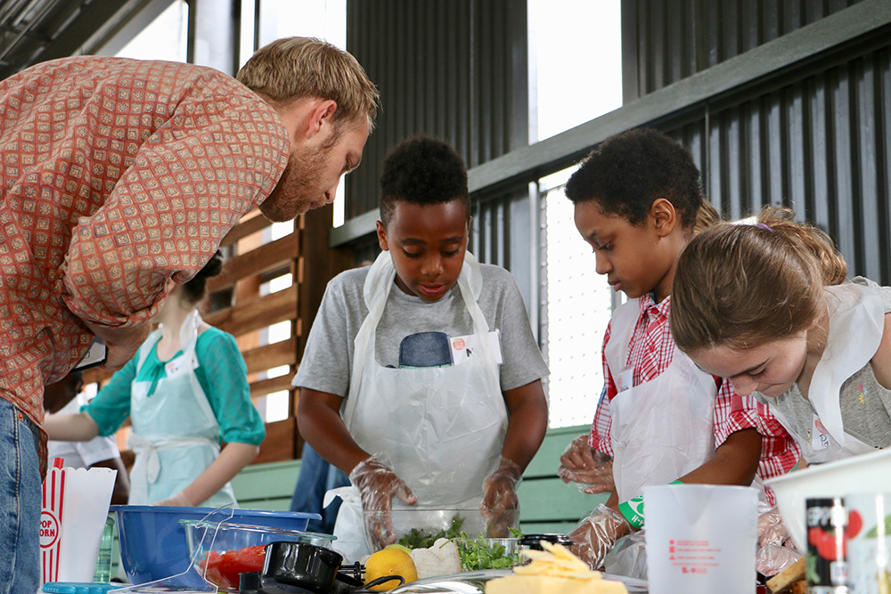 Chef Daniel Peach of Botiwalla checks in on school-aged chefs Nile Smith of Roswell North Elementary School, Isaiah Farrow of Georgia Connections Academy, and Parker Payne of Woodward Academy as they put the finishing touches on their kale salad and grilled cheese sandwich during the inaugural Fulton Fresh Kids Cooking Competition.