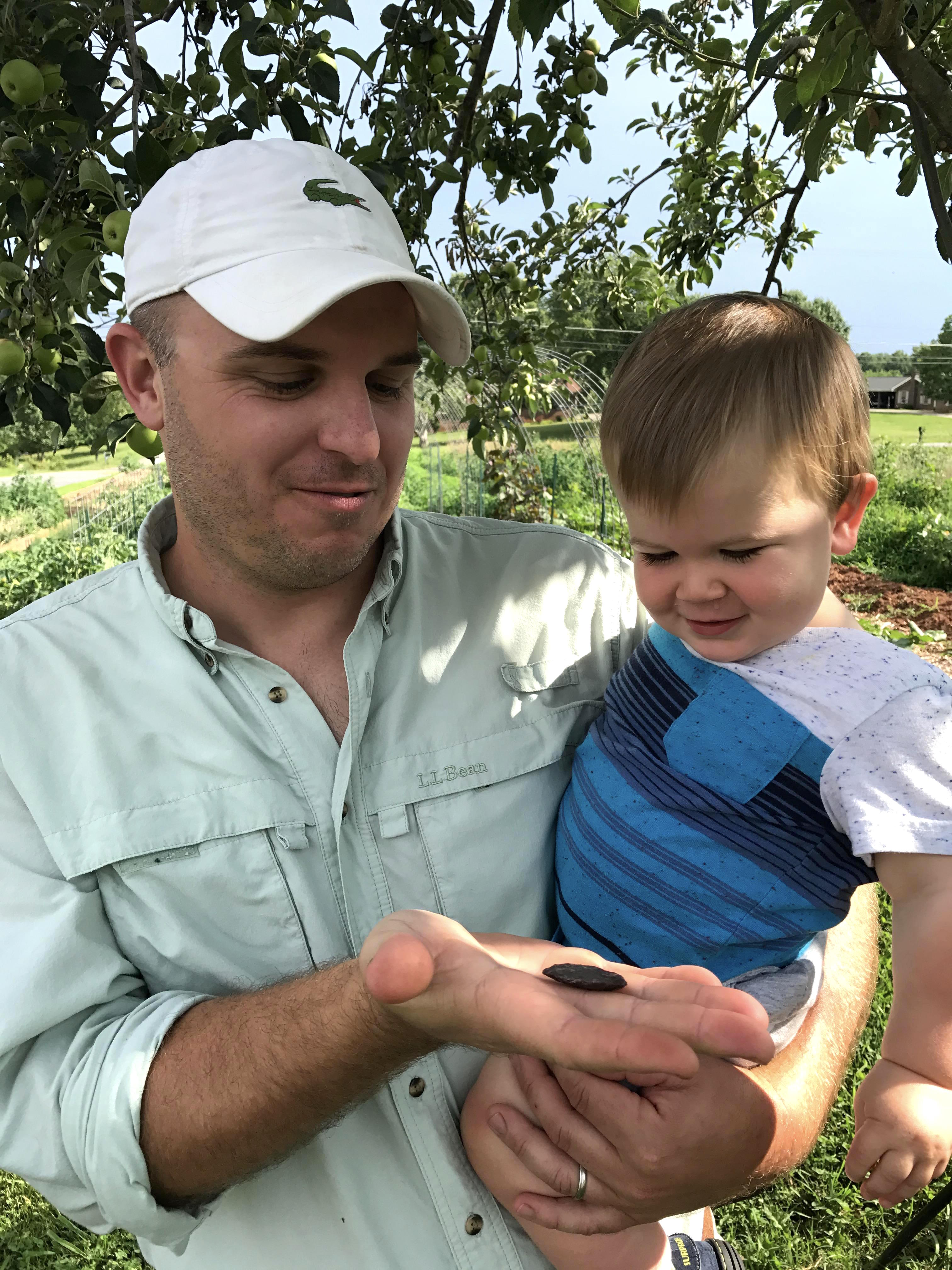 University of Georgia Cooperative Extension Agent Josh Fuder and his son, Graham, inspect an ancient artifact he uncovered in his backyard garden. As a child, Fuder loved digging in the soil for buried treasures and pretending to be an archeologist. He hopes his son inherits his love of items from days gone by.