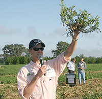 UGA peanut entomologist Mark Abney holds up a peanut plant during the Georgia Peanut Tour in 2016.