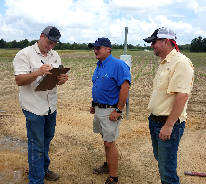 New UGA Extension water educators John Loughridge (left) and Luke Crosson (right) collect center pivot information from a landowner, David Burk (middle).
