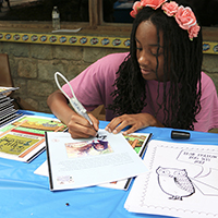 Lavendar Harris, 16-year-old Georgia 4-H'er and a volunteer at Bear Hollow Zoo in Athens-Clarke County, signs copies of a coloring book that she created as a fundraiser for the zoo. Harris is a home-schooled student and Newton County, Georgia, 4-H Club member. The coloring book is the keystone of her Georgia 4-H Leadership in Action project.