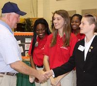 Secretary of Agriculture Sonny Perdue met with a group of select Georgia 4-H'ers on Friday, Oct. 6, in recognition of National 4-H Week, held Oct. 2-6. Perdue is shown being greeted by Pulaski County 4-H member Cooper Hardy. The secretary and the students toured the 4-H exhibits at the Georgia National Fair in Perry, Georgia, the former Georgia governor's hometown. He also heard presentations from three Georgia 4-H'ers: Amelia Day of Houston County, Angel Austin of Ben Hill County and Evie Woodward of Coffee County.