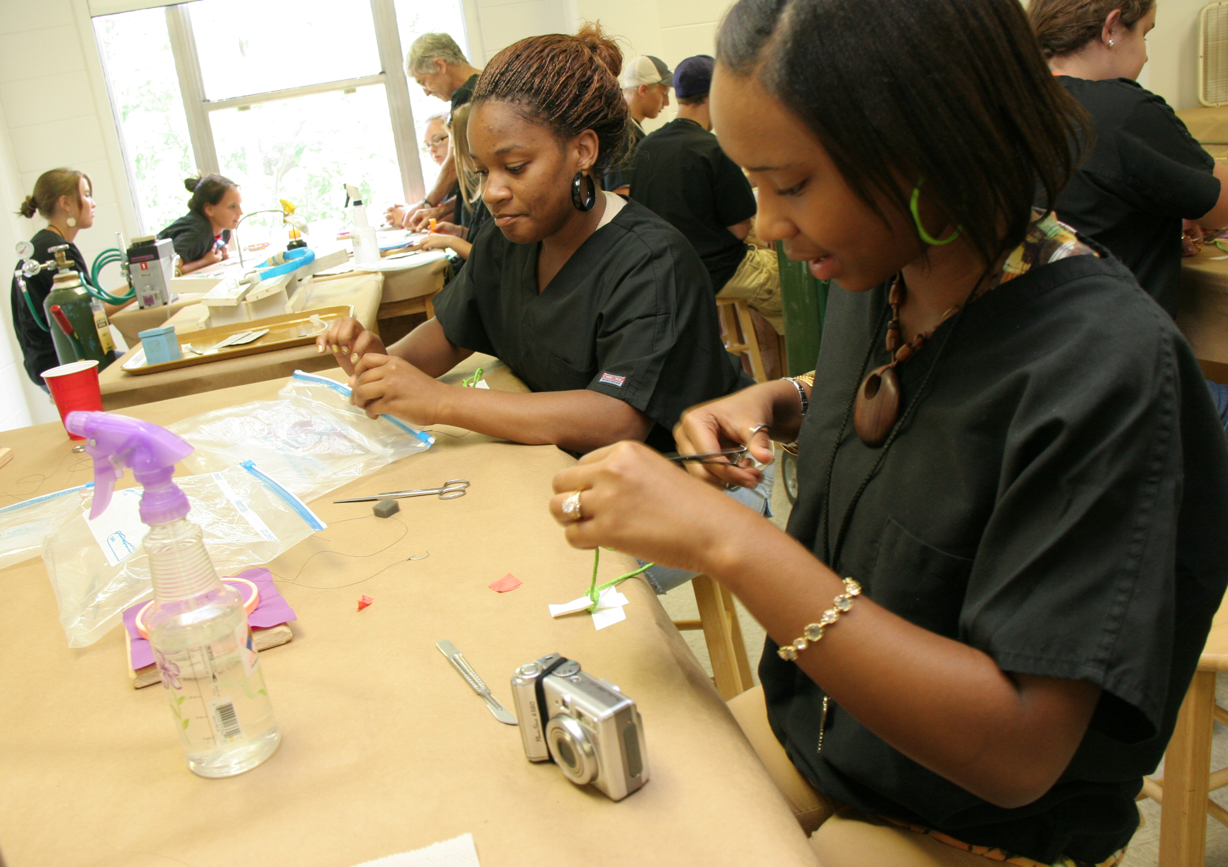 High school students practice their suturing skills.