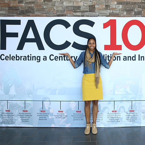 The UGA College of Family and Consumer Sciences will celebrate its 100 year anniversary in 2018.   Alumni Director Alexis Morgan poses with a banner timeline celebrating the centennial.
