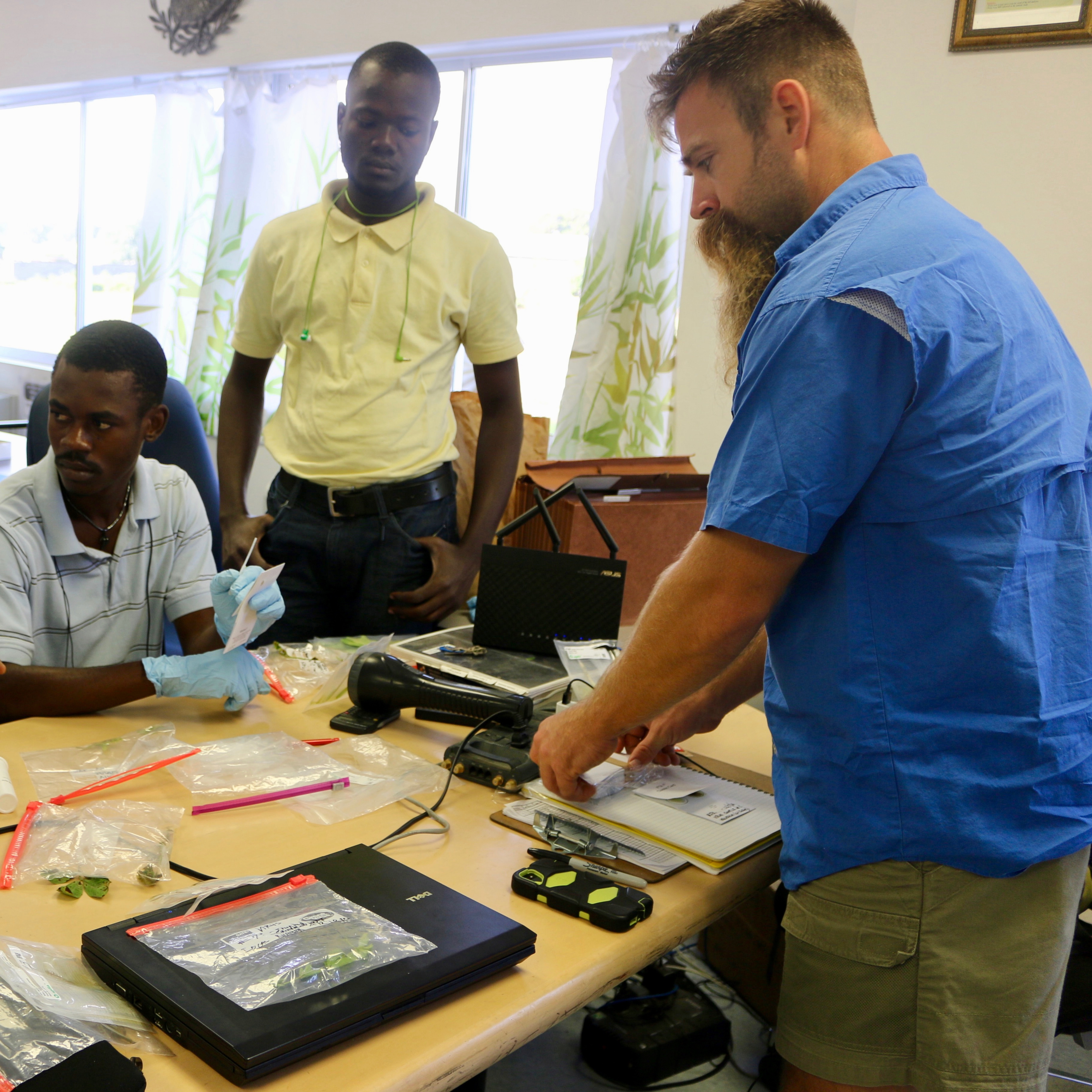 UGA graduate student Abraham Fulmer shows Haitian agronomists working at the Meds & Food for Kids facility in Cap-Haitian, Haiti, how to identify leaf spot in peanut in December 2016. Fulmer, who recently completed a PhD in plant pathology at the University of Georgia, did research in Haiti with the Feed the Future Peanut & Mycotoxin Innovation Lab, which was at UGA from 2012 to 2017 . The federal government recently awarded UGA another five-year peanut research program to battle global food insecurity.