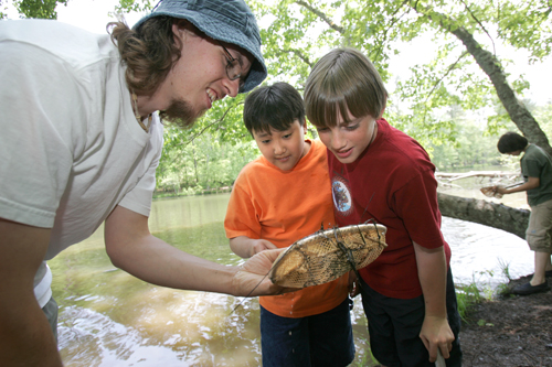 Rocky Mount's Tyler Romeu (left) and Jonathan Miller (right) show the contents of their net to instructor Chris Edmonds (far left) during lake ecology class while on an environmental education field trip at Rock Eagle 4-H center in Eatonton, Tuesday, May 3, 2005.