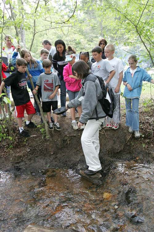 Instructor Cat Rosario, shows her panning prospect from a creek as Alpharetta Elementary students watch and listen to her demonstration before trying it themselves during environmental education at Wahsega 4-H camp in Dahlonega, Thursday, April 28, 2005.