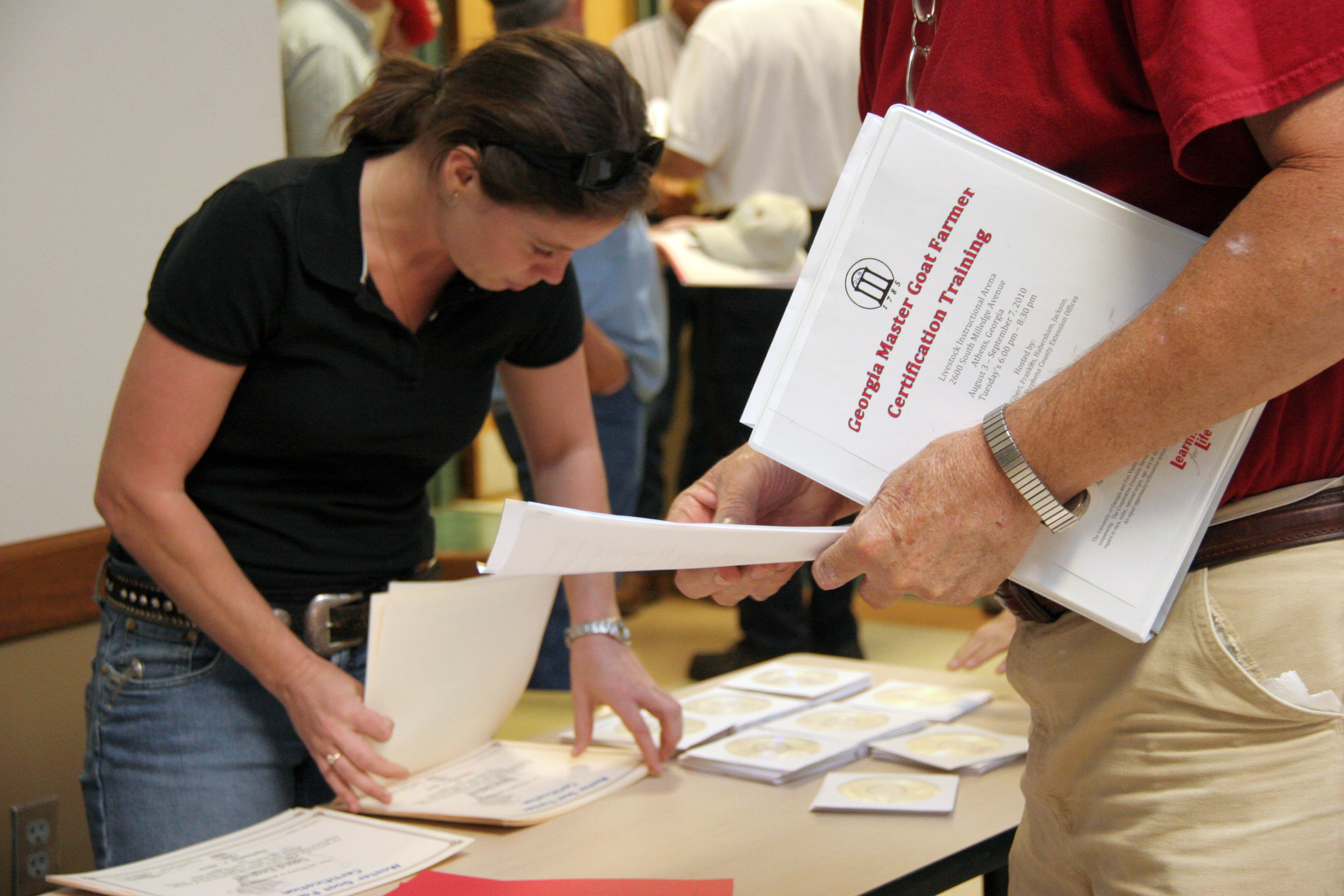 Jasper County Extension agent Lucy Ray, left, hands Master Goat Farmer participants the final paperwork of the program.