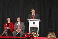 UGA President Jere W. Morehead speaks at the Agricultural Research Building rededication as CAES Dean Samuel Pardue and student ambassador Kelly Paulk listen on stage.