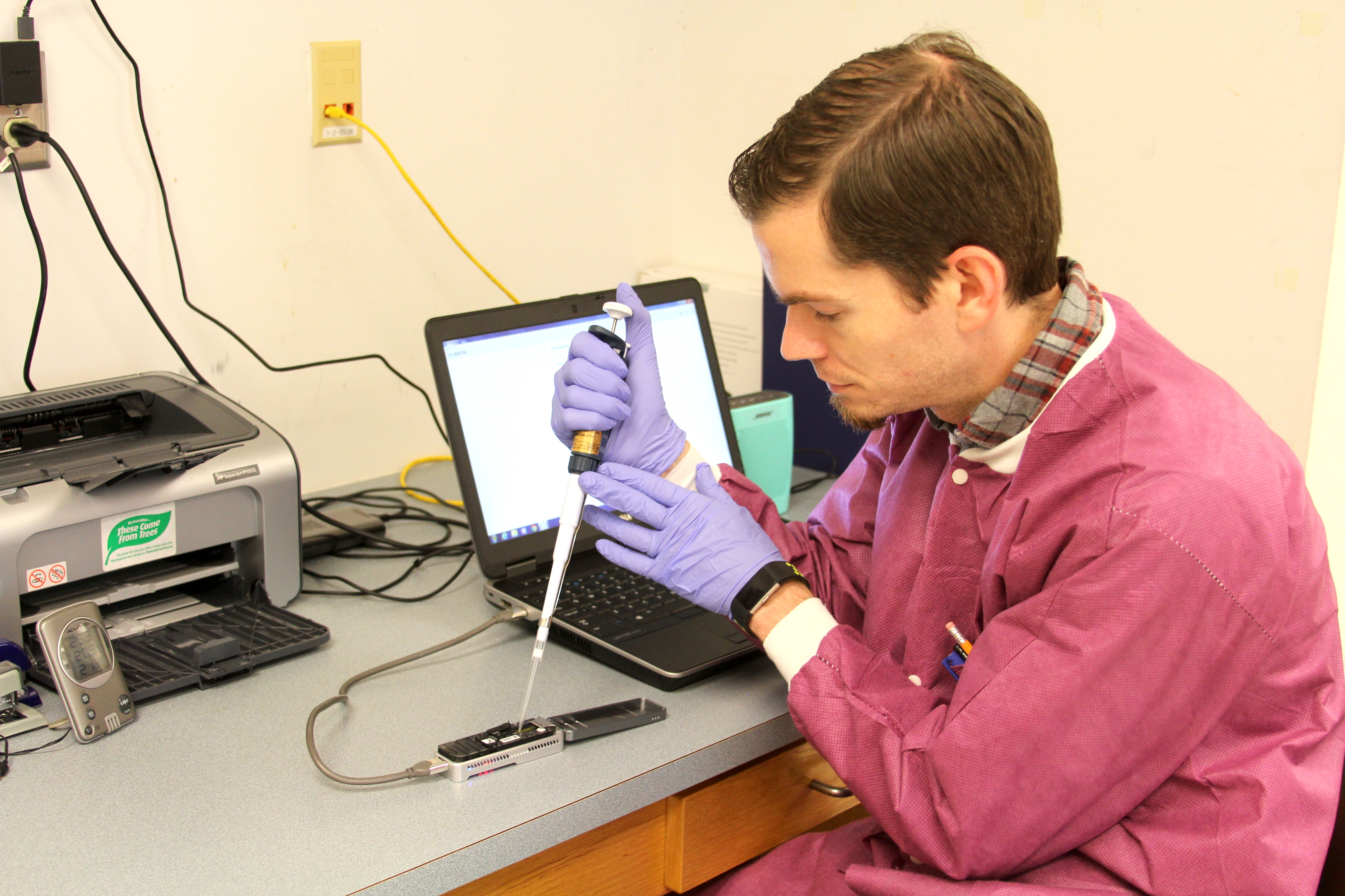 """University of Georgia Research Professional David Mann works on a portable sequencer in food scientist Xiangyu Deng's laboratory in the UGA Center for Food Safety in Griffin, Georgia. Deng has developed a one-step method of detecting and subtyping food pathogens called """"metagenomics analysis."""" The method is much quicker than traditional methods, and time is essential during outbreaks of foodborne illness."""