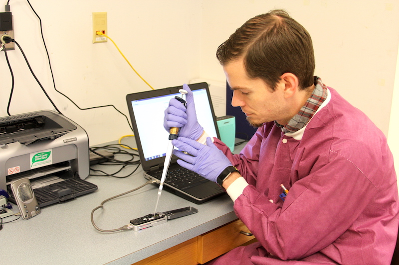 "University of Georgia Research Professional David Mann works on a portable sequencer in food scientist Xiangyu Deng's laboratory in the UGA Center for Food Safety in Griffin, Georgia. Deng has developed a one-step method of detecting and subtyping food pathogens called ""metagenomics analysis."" The method is much quicker than traditional methods, and time is essential during outbreaks of foodborne illness."