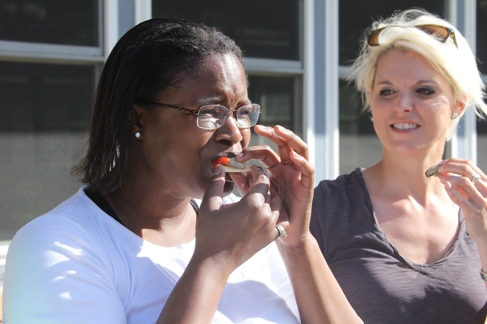 Kisha Faulk tries her first roasted oyster while her coworker Barbara Worley looks on. The two women were among the participants in a recent Ocean to Table workshop designed to increase consumers' and UGA Extension agents' knowledge and awareness of Georgia seafood.