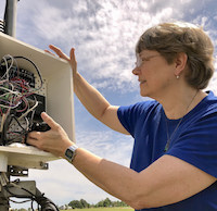 On a sunny day in 2018, Pam Knox checks the data logger at the University of Georgia weather station on the Durham Horticulture Farm in Watkinsville, Georgia.