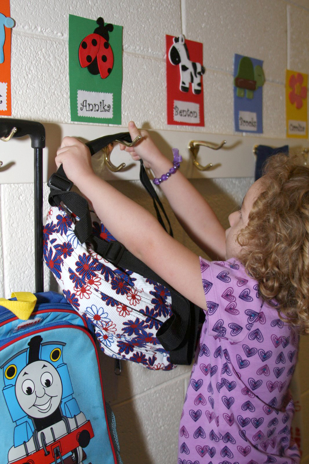 A student hangs her bookbag on a peg outside her classroom door.