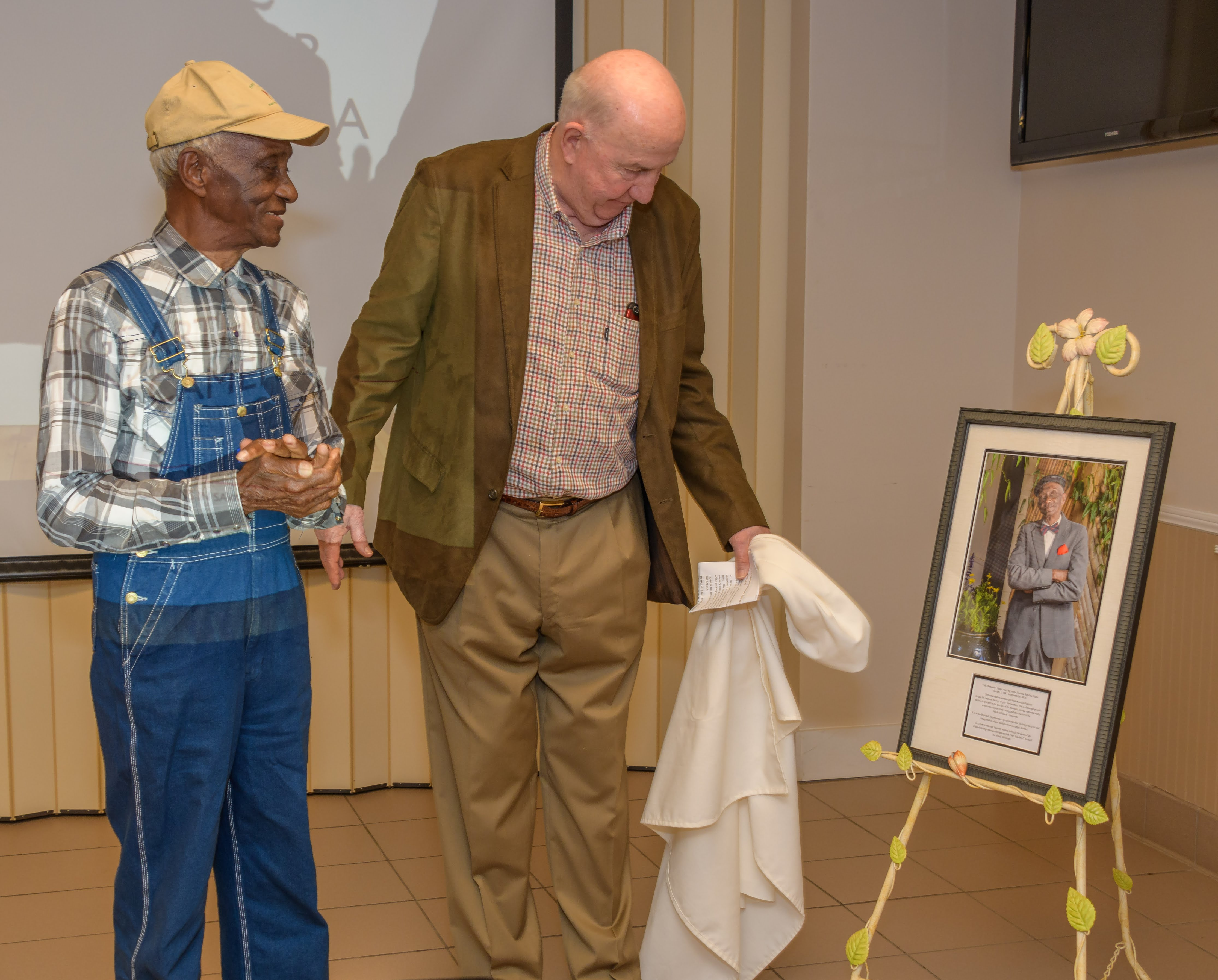 The Friends of the Coastal Gardens (FOCG) recently named a classroom in honor of retired groundskeeper Frank Williams. The Friends wanted to show their appreciation for the 30 years of hard work and dedication he gave to the University of Georgia Coastal Georgia Botanical Garden at the Historic Bamboo Farm in Savannah, Georgia. Williams is shown (left) watching FOCG President Dr. Jim Andrews unveil one of three photographs that now adorn the walls of the Frank Williams Classroom.