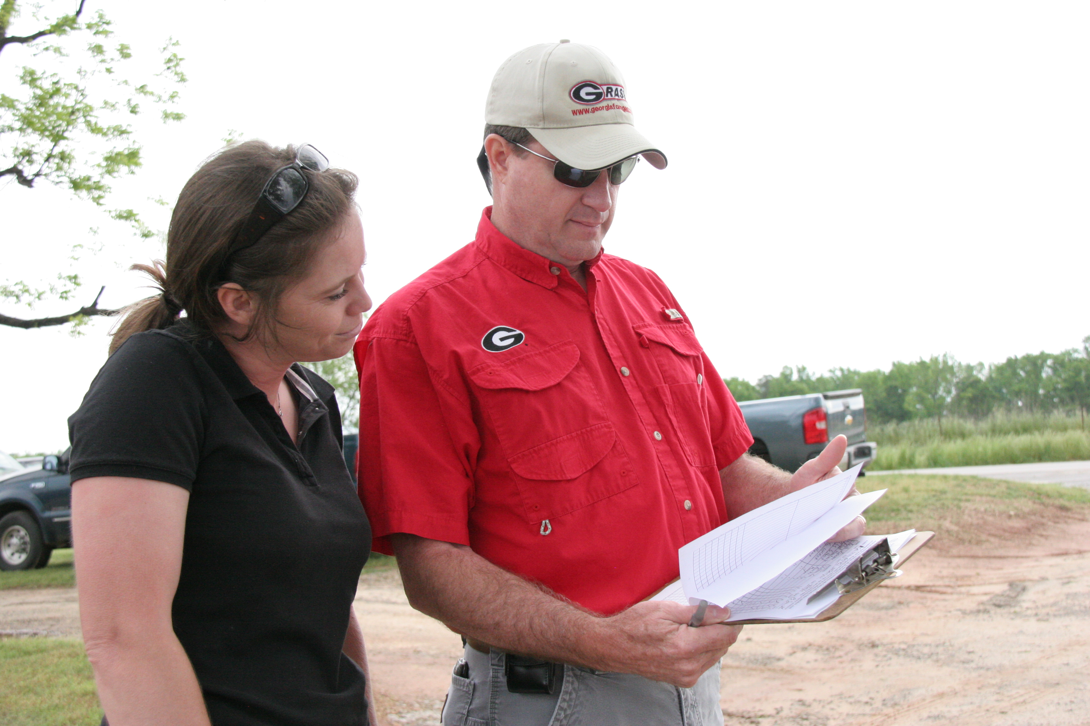 Bobby Smith, newly appointed district director for UGA Cooperative Extension's Northeast Georgia district, reviews the schedule at a field day in Morgan County with current Morgan County Extension Coordinator Lucy Ray.