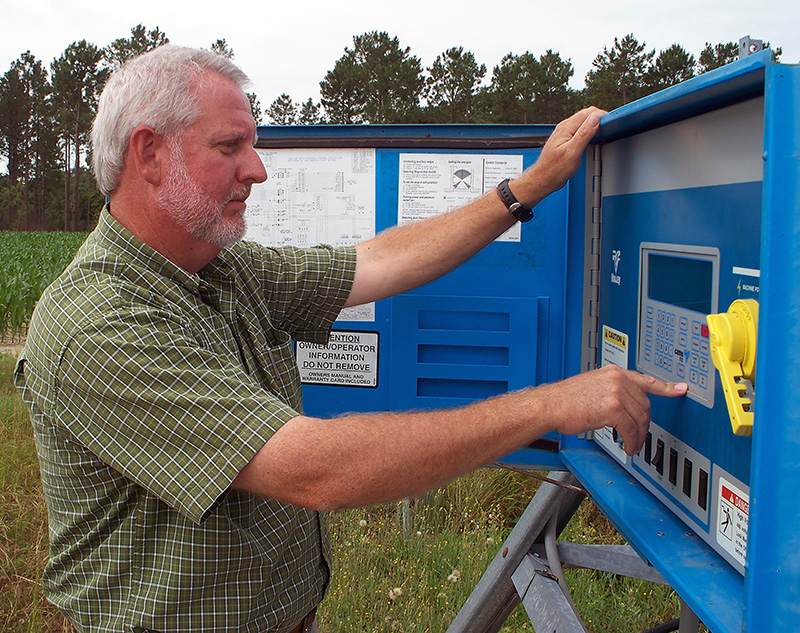 Calvin Perry, superintendent of Stripling Irrigation Research Park, examines an irrigation box in this 2014 photo.