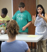 Gwinnett County Family and Consumer Sciences Agent Ines Beltran teaches people how to become, and stay, healthier. She is shown teaching a group of 4-H students how to make healthy food choices.