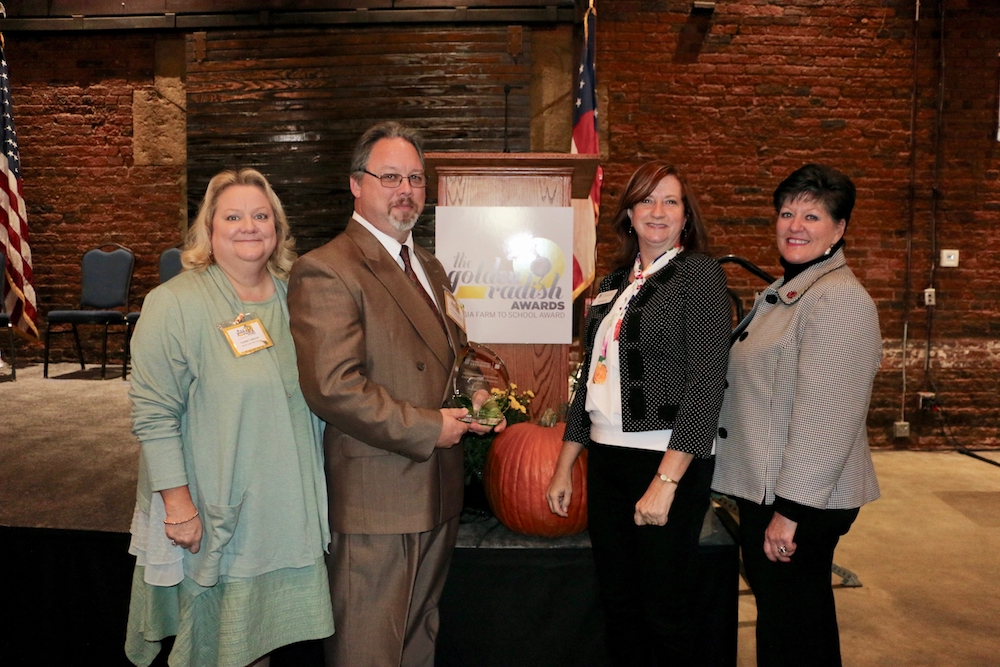 Tammy Cheely, University of Georgia Cooperative Extension county coordinator for Warren County; Scott Richardson, technical education and nutrition director for Warren County Schools; Becky Griffin, UGA Extension community and school garden coordinator and Laura Perry Johnson, associate dean and director of UGA Extension celebrate the presentation of UGA Extensions inaugural Golden Radish Outstanding Extension Farm to School Program Award.