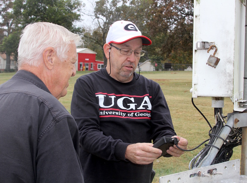 University of Georgia employees Eddie Eddenfield (r) and Dennis Evans check readings at the UGA weather station on the campus in Griffin, Georgia.  Eddenfield and Evans are responsible for making sure each of the network's 86 stations operate properly.