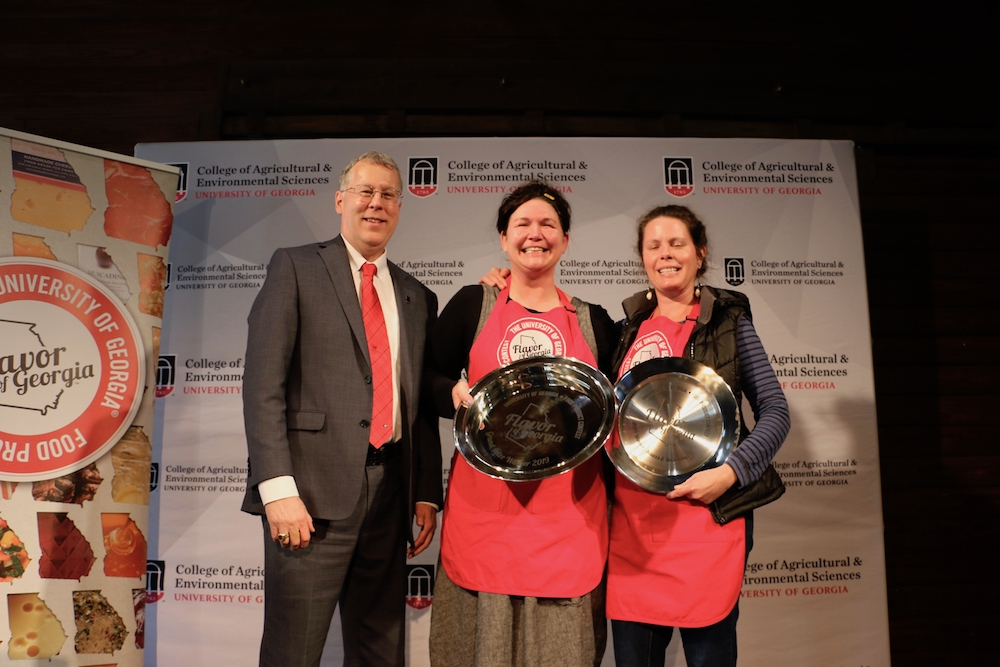 College of Agricultural and Environmental Sciences Dean Sam Pardue congratulates Suzy Sheffield of Atlanta's Beautiful Briny Sea and Holly Hollifield on their grand prize win at Flavor of Georgia 2019.