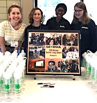 A group of Georgia 4-H members is using a grant from the Robert Wood Johnson Foundation and National 4-H Council to teach their fellow 4-H'ers to make healthier snack and beverage choices. The students are showing handing out water bottles at the Georgia 4-H Senior Conference in April.