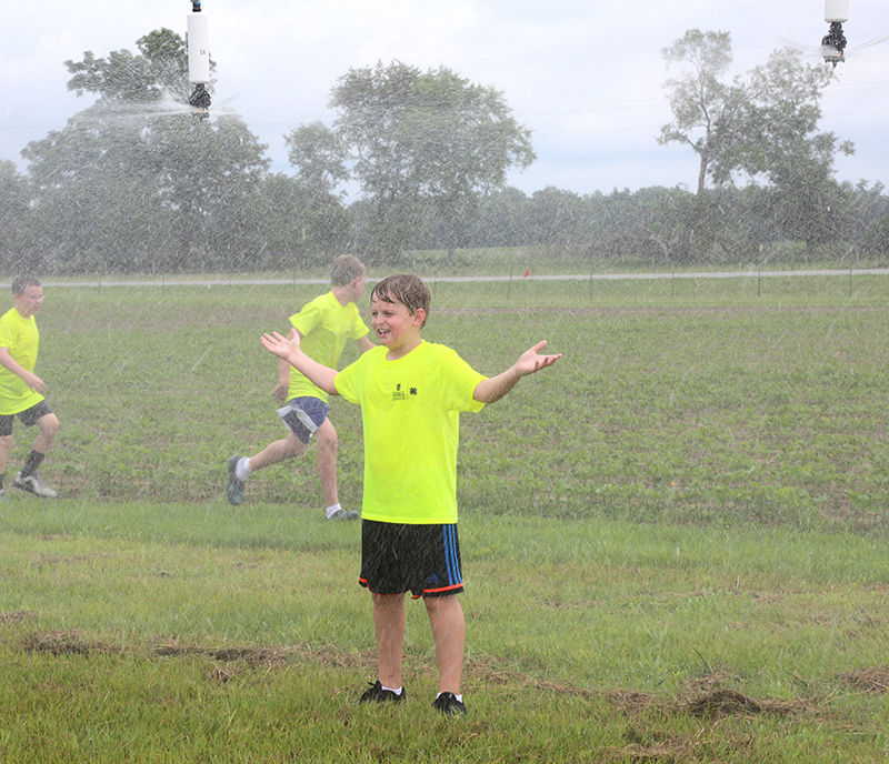4-H student Jacob Moore enjoys getting cooled off from the irrigation pivot during the 4-H2O camp at Stripling research park on June 12, 2019.