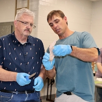 Brinson Brock, agriculture teacher at Sumpter County Middle School, and North Oconee County High School agriculture teacher Tim Griffeth break down a broiler to help learn about the anatomy of a chicken.