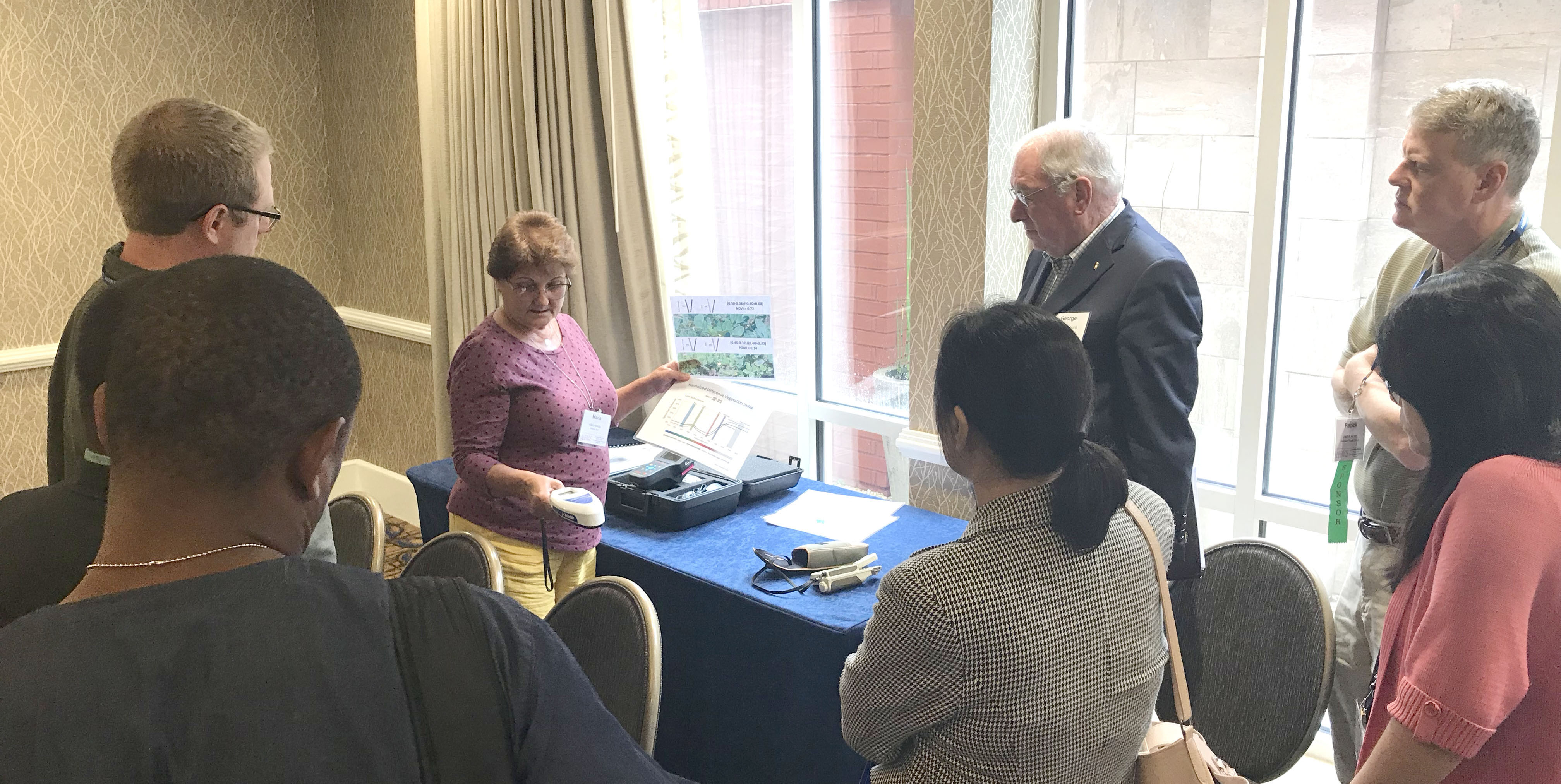 Virginia Tech plant pathologist and Peanut Innovation Lab scientist Maria Balota demonstrates some of the sensors she uses in the high throughput phenotyping project to attendees at the 51st annual American Peanut Research and Education Society meeting in Auburn, Ala. which was held July 9-11, 2019.