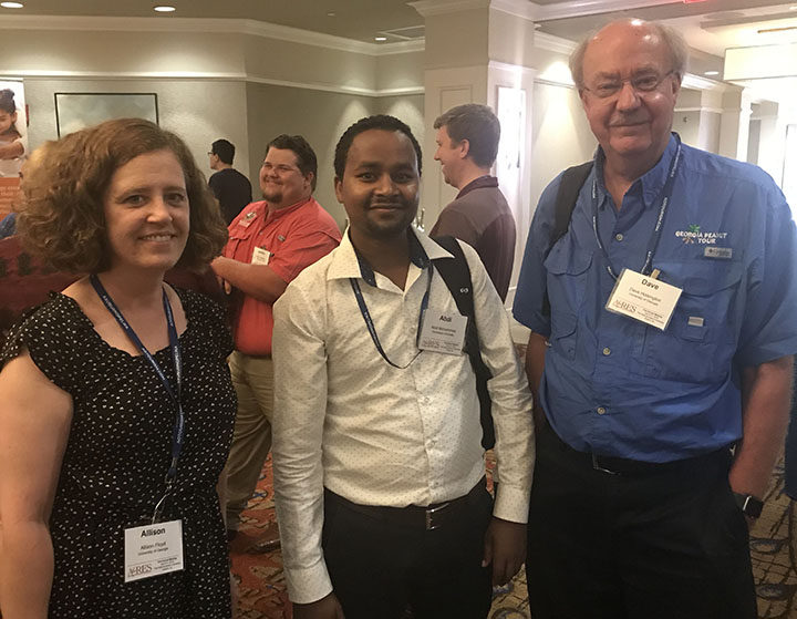 "Peanut Innovation Lab Director Dave Hoisington (right) and Communications Coordinator Allison Floyd are pictured with Abdi Hassen, an Ethiopian peanut researcher and lab collaborator. Hassen presented at the conference, which was themed ""Peanuts Around the World."""