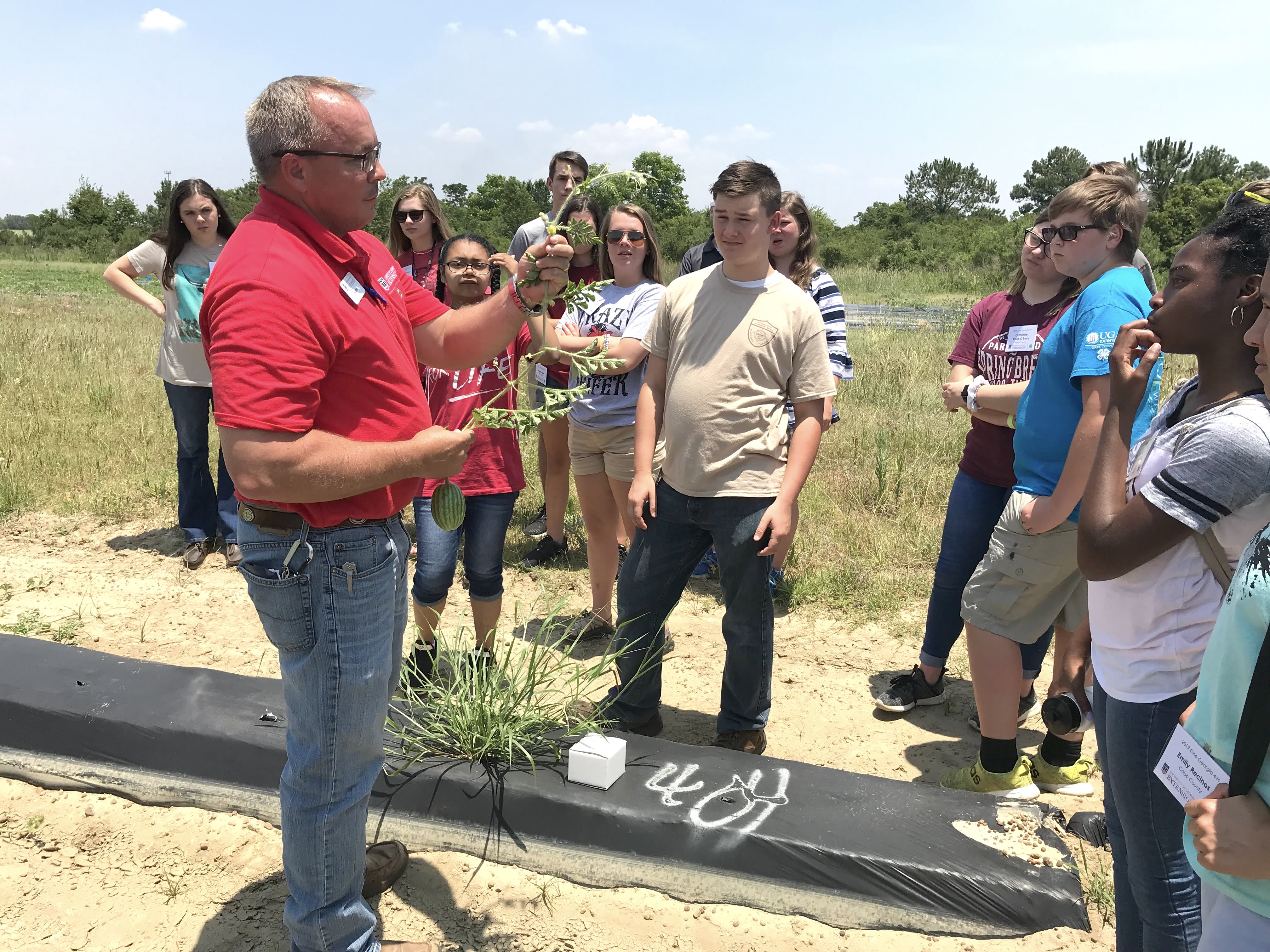 Students in the One Georgia program are shown learning about watermelon farming from Sumter County Extension Agent Bill Starr. While in south Georgia, the students also visited cotton fields and saw turfgrass sod harvested.