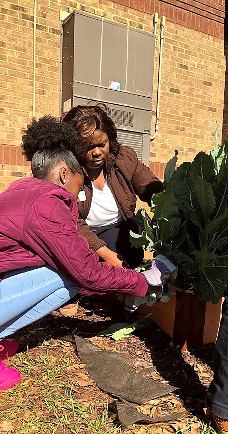 Sumter County 4-H Agent Crystal Perry helps a student care for the plants in the garden bed as part of the ROCKETS program.