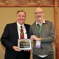 Jim McFerson, director of Washington State University's Tree Fruit Research and Extension Center, presents famed USDA turfgrass breeder Wayne Hanna, UGA professor of crop and soil sciences, with the National Association of Plant Breeders (NAPB) Lifetime Achievement Award at the NAPB's annual meeting in Pine Mountain, Georgia.