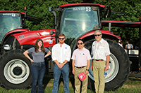 From right, UGA-Tifton Assistant Dean Joe West, UGA Provost S. Jack Hu and Tidewater representatives pose for a picture in front of one of the tractors donated to UGA-Tifton this fall.