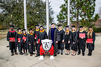 UGA-Tifton Assistant Dean Joe West poses for a picture in front of campus with the 2019 fall graduates.