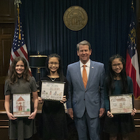 Fifth-graders, from left, Emi Hoang, Caitlin Smith and Gia Hoang, receive kudos from Gov. Brian Kemp on their Radon Awareness Posters. Gia Hoang won first place in the UGA Cooperative Extension Radon Awareness Poster Contest. Caitlin Smith and Emi Hoang, won second and third places respectively.