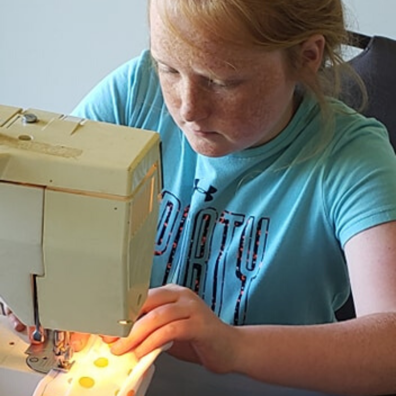 Georgia 4-H'er uses Project Achievement skills to sew masks for children.