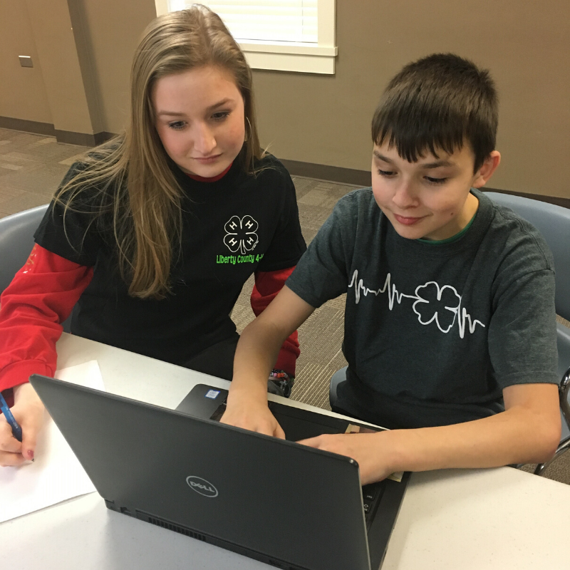 Georgia 4-H youth and agent on a computer.