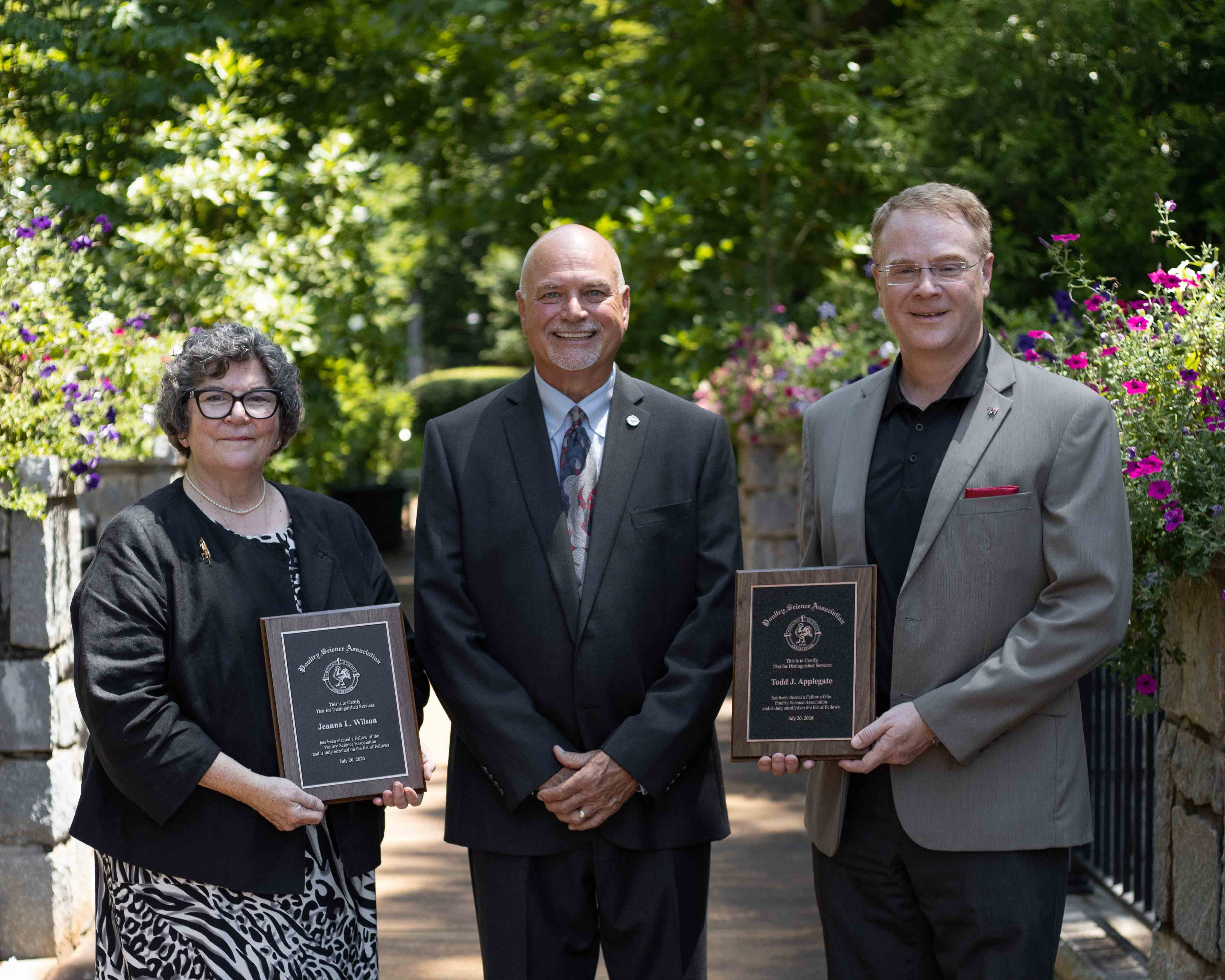UGA Department of Poultry Science Professor Jeanna L. Wilson (left) and Professor and Department Head Todd Applegate (right) receive their Fellow awards from Poultry Science Association President Don McIntyre.