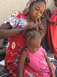 An expecting woman, already the mother of two daughters, braids a child's hair in a rural village in the Kaolack region of Senegal in February 2020. While she normally would work either in the fields or processing peanuts, she is taking a break from work in her last month of pregnancy. Women often bear responsibility both for reproduction (caring for children) and production (growing crops), and since peanut is grown primarily by women, researchers wonder whether time-strapped women are more or less likely to adopt new technologies in agriculture. Researchers from the University of California-Santa Barbara, the University of Georgia and Gaston Berger University in Senegal conducted an ethnographic assessment of women's lives in Senegal earlier this year and plan to implement a system next year that will use biometric devices and voice recorders to capture a broader, more objective view of the work that takes up women's time. (Photo by Jacqueline Banks/UC-Santa Barbara)