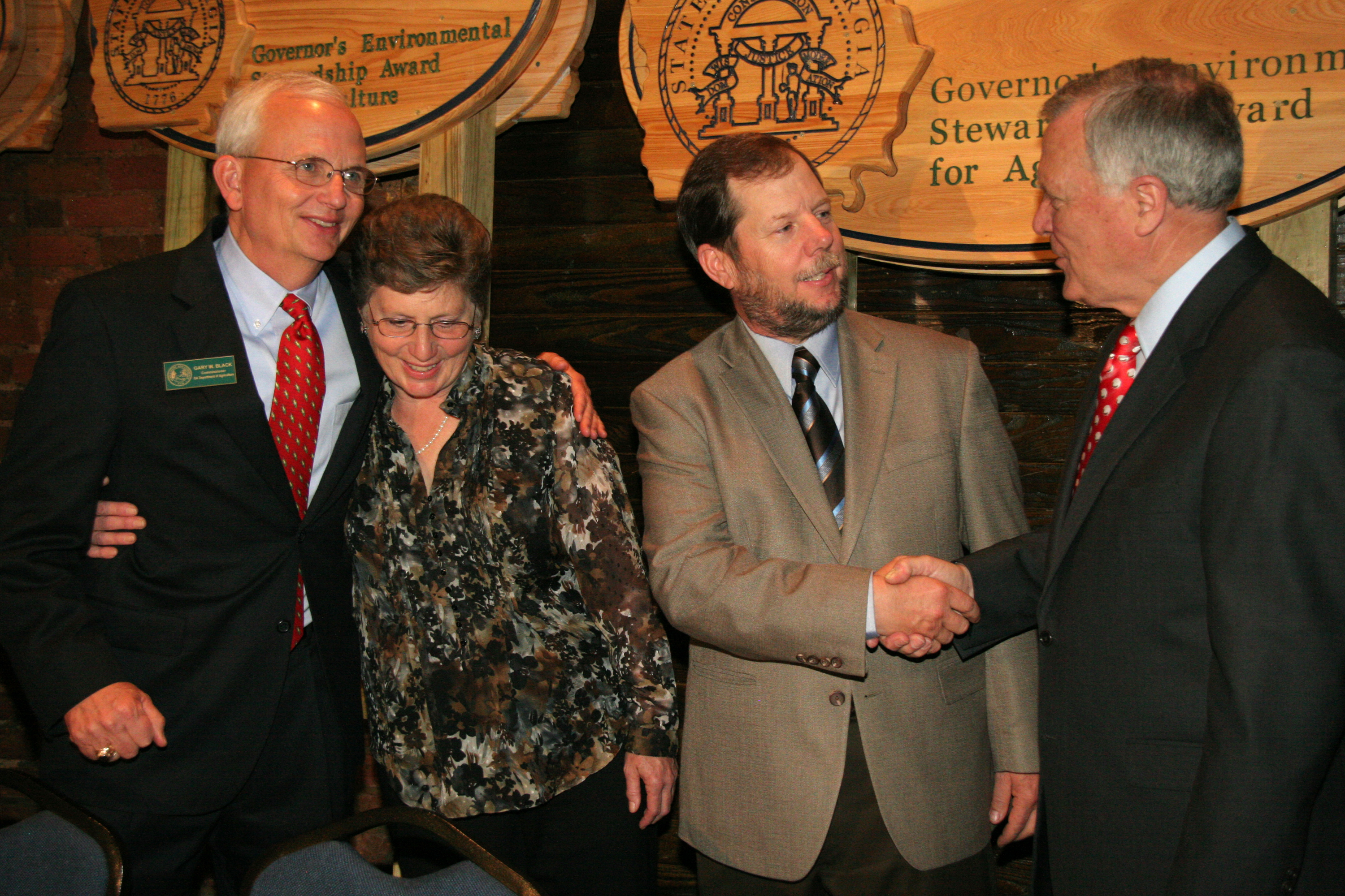 Everett Williams, middle right, is congratulated by Georgia Gov. Nathan Deal, right, after winning the 2011 Georgia Environmental Stewardship Award on March 22 at Georgia Ag Day in Atlanta. At left, Carol Williams accepts congratulations from Georgia Agriculture Commissioner Gary Black.