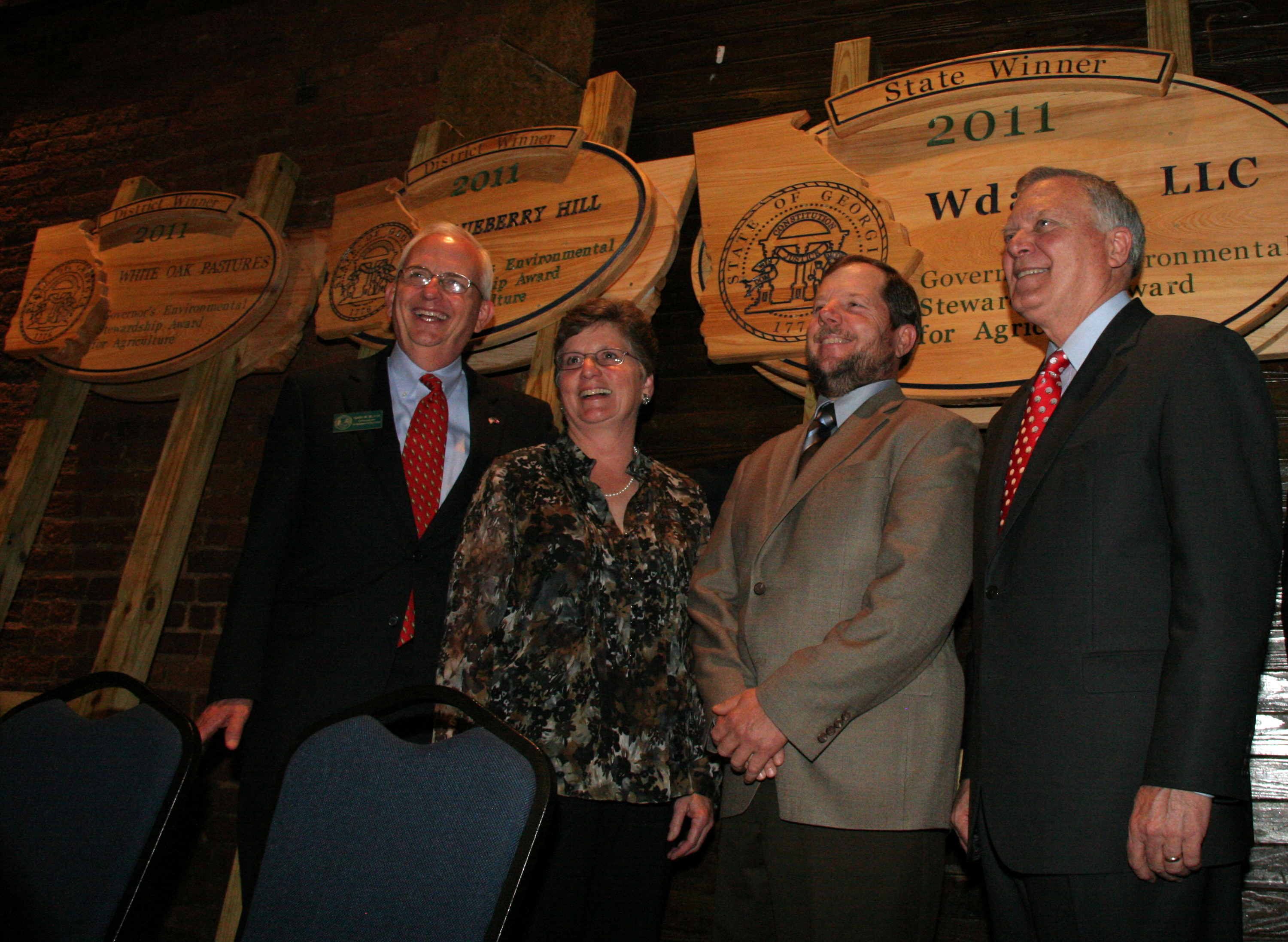 Carol and Everett Williams, center, celebrate their win and their new Georgia Environmental Stewardship sign along with Georgia Agriculture Commissioner Gary Black, left, and Gov. Nathan Deal, right.